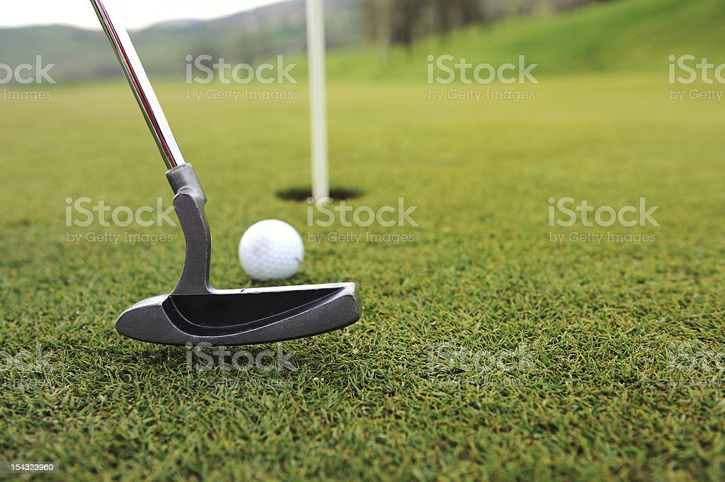 Golf ball and stick on green grass stock photo