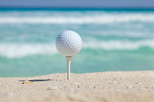 Golf ball and tee on beach with ocean waves behind