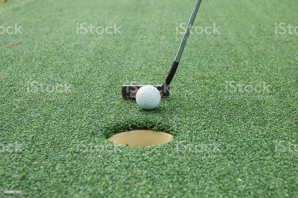 golf ball and tee on green course in front of driver