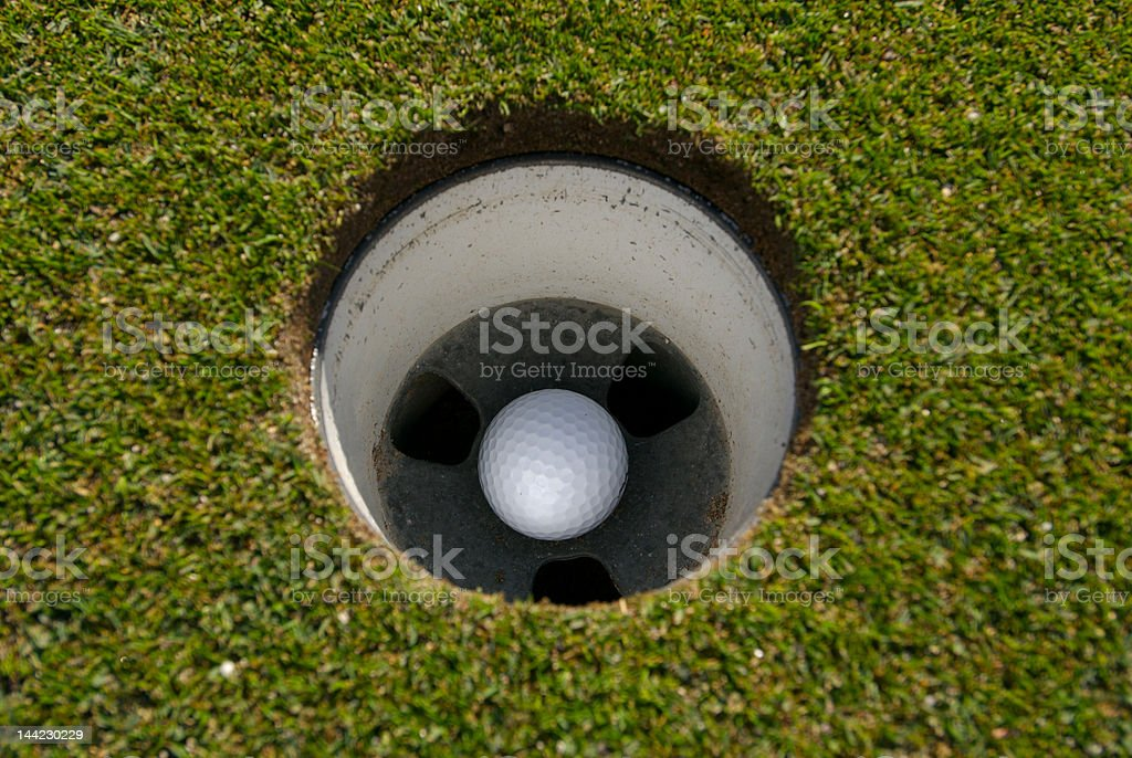 Golf ball at rest in the hole stock photo