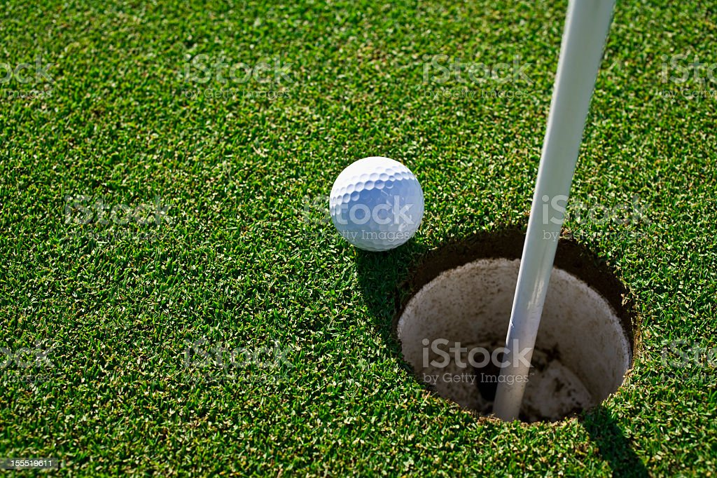 Golf ball at the edge of a hole on the green stock photo