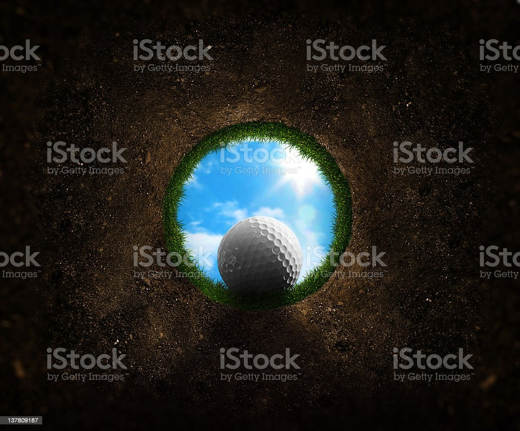 Golf ball falling into the cup stock photo