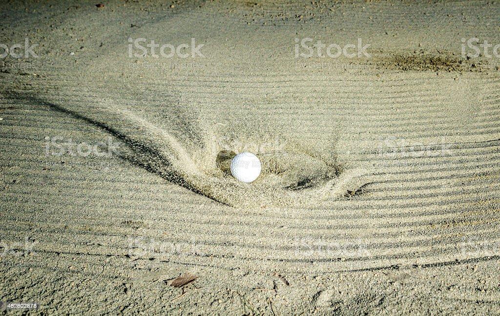 Golf ball hitting the sand bunker stock photo