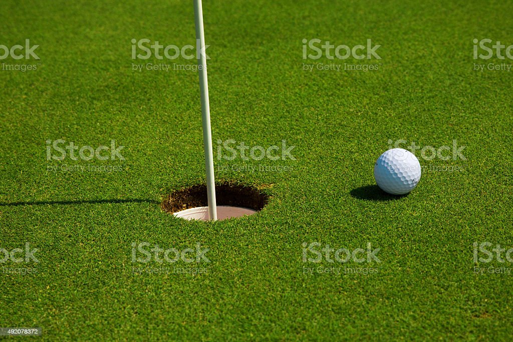 Golf ball in a course and hole stock photo