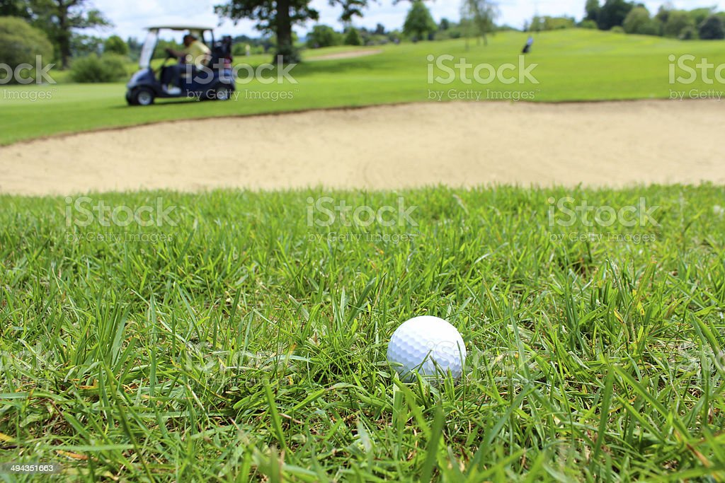 Golf ball in grass, with golf buggy and sandy bunker royalty-free stock photo
