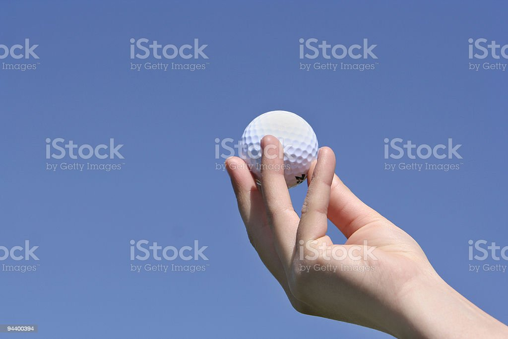 golf ball in my hand with a blue sky royalty-free stock photo