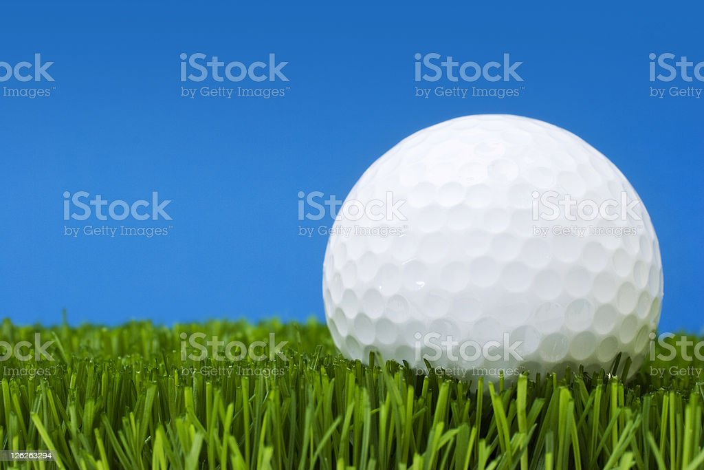 Golf ball in perfect grass against blue background royalty-free stock photo