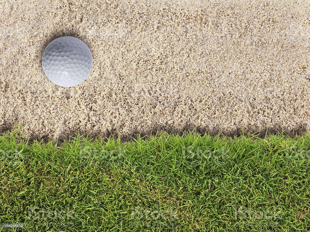 Golf ball in sand bunker near fresh green grass stock photo