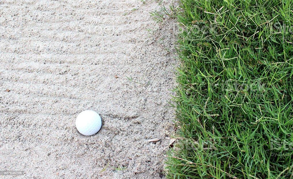 golf ball in sand bunker stock photo