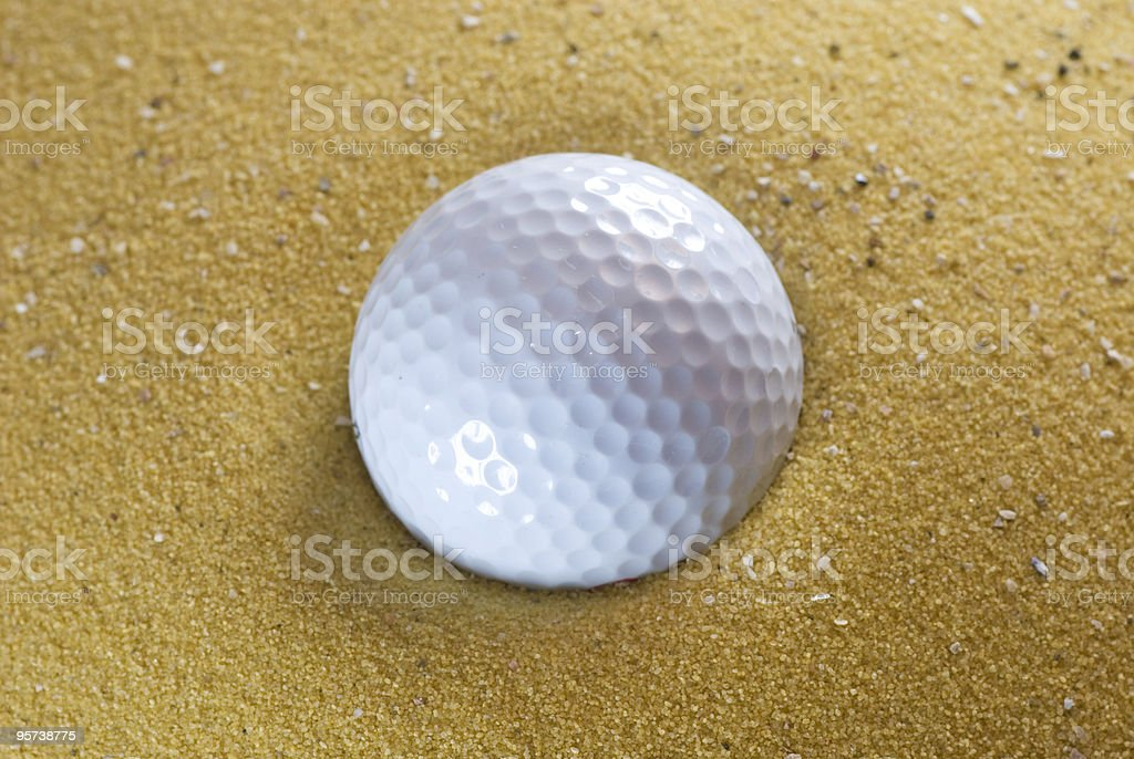 Golfball in sand royalty-free stock photo