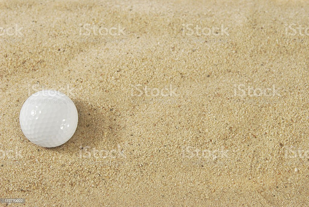 Golf ball in sand trap royalty-free stock photo