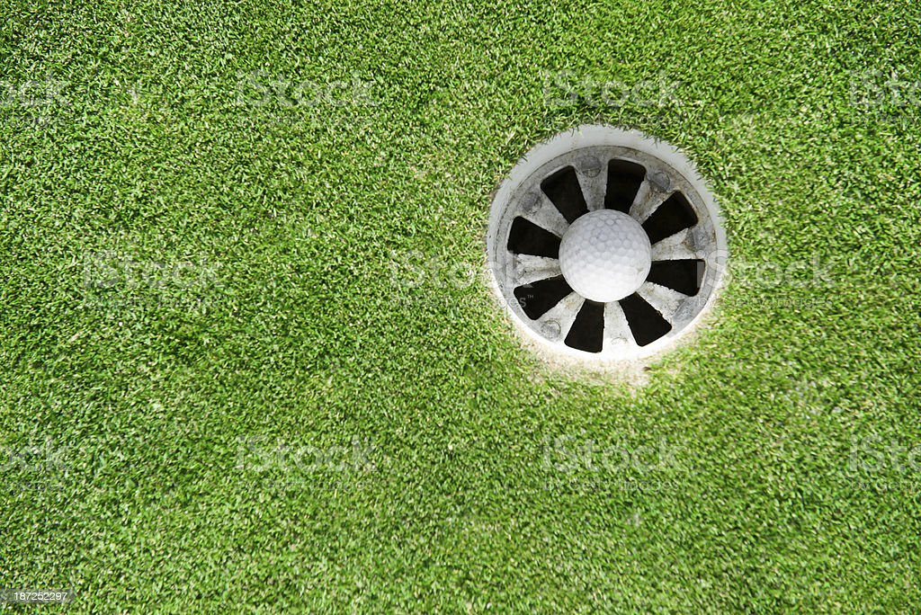 golf ball into the hole stock photo