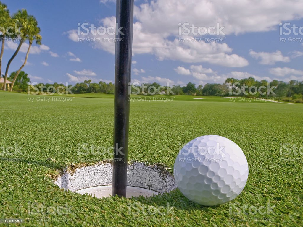 golf ball lies just at the hole royalty-free stock photo