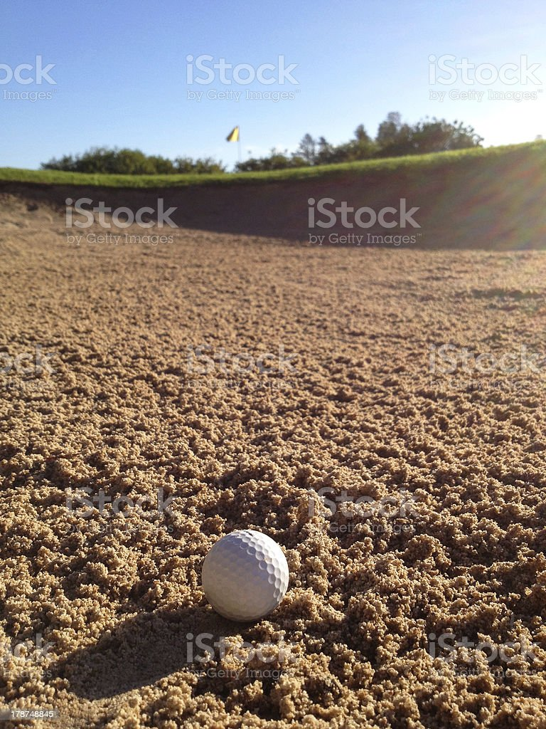 Golf ball lying in bunker with green and pin royalty-free stock photo