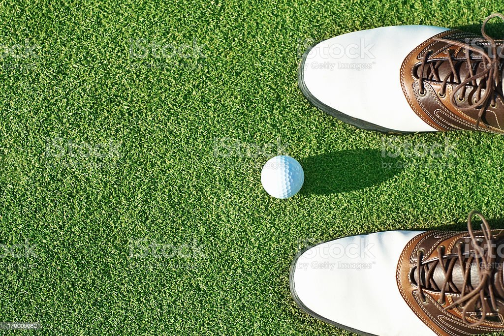 Golf ball near a pair of shoes stock photo