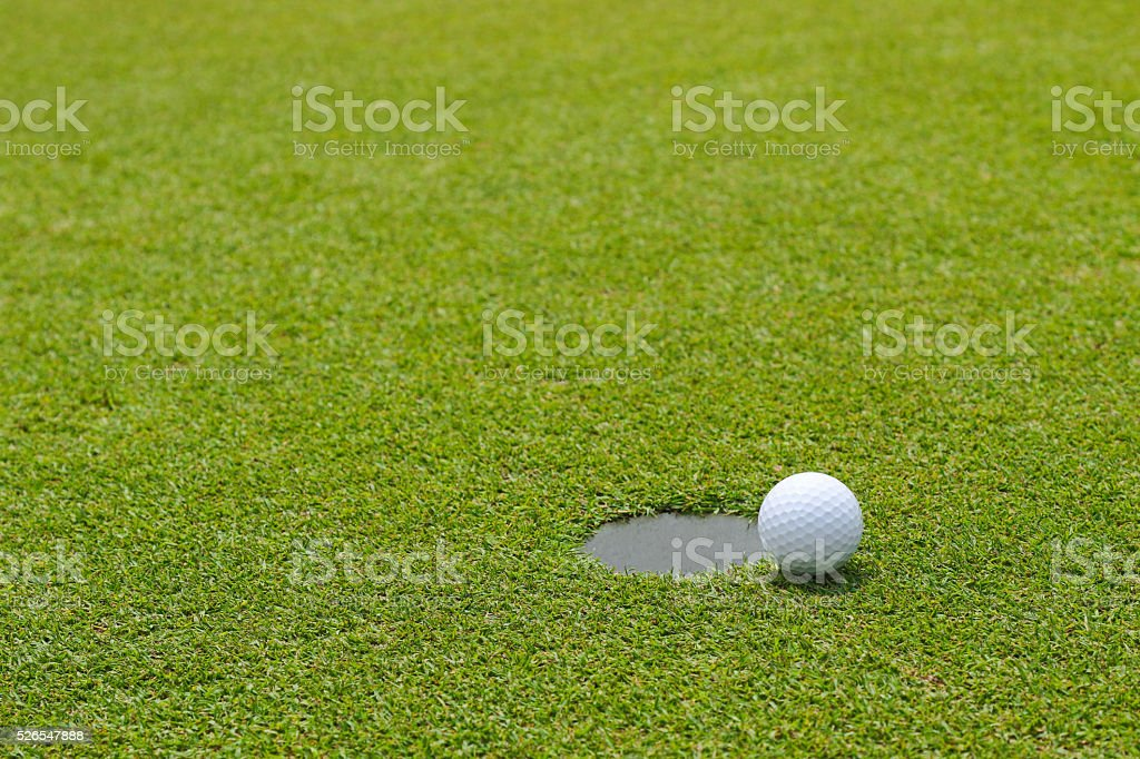 Golf ball near putting cup hold at putting green stock photo