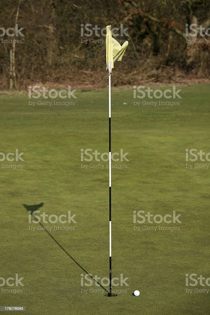 Golf Ball next to a hole royalty-free stock photo
