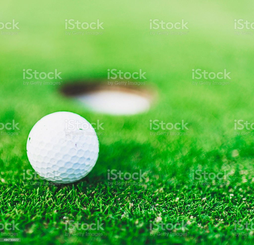 Golf Ball Next to Cup on Putting Green stock photo