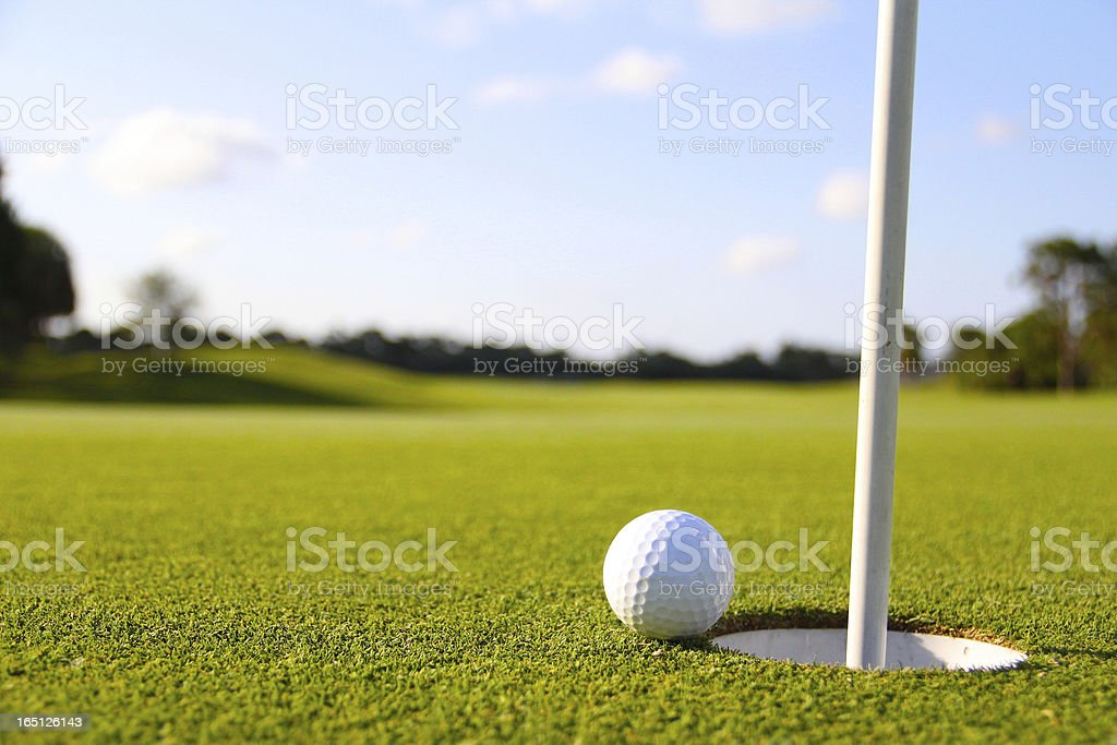 golf ball next to the hole and flag stock photo