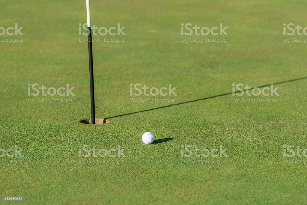 Golf ball on a perfect green next to the hole and pin with shadows