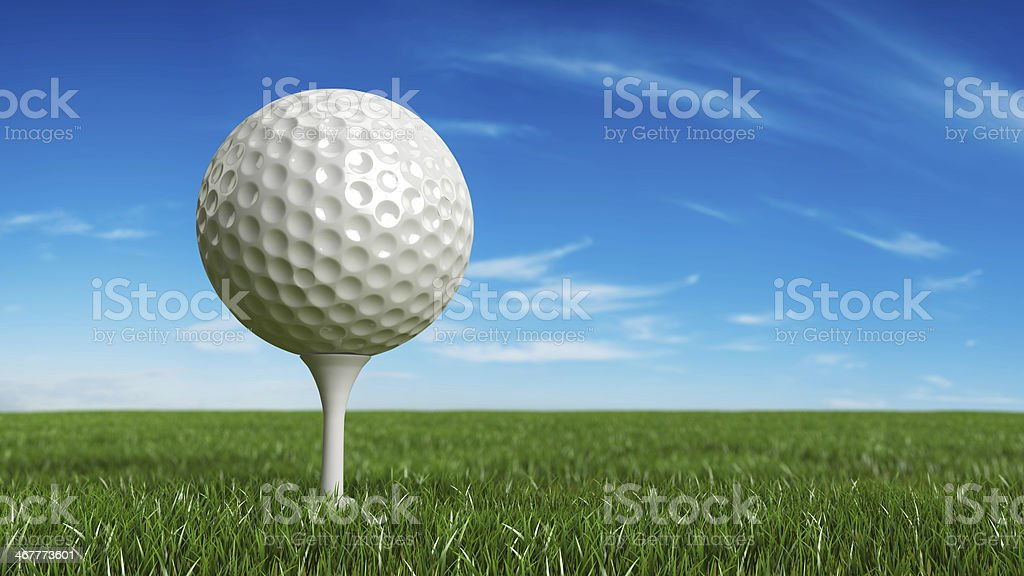 A golf ball on a tee on green grass stock photo