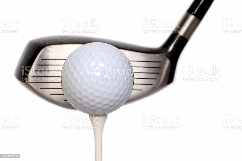 Golf ball on a tee with the head of a golf club next to it stock photo