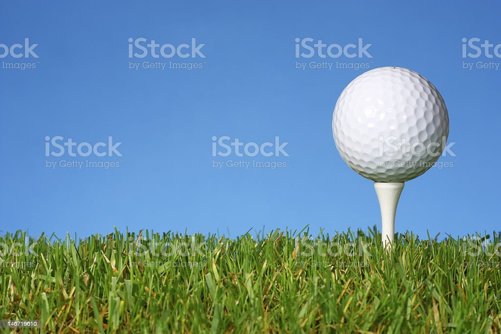 Golf ball on a white tee with lush grass. stock photo