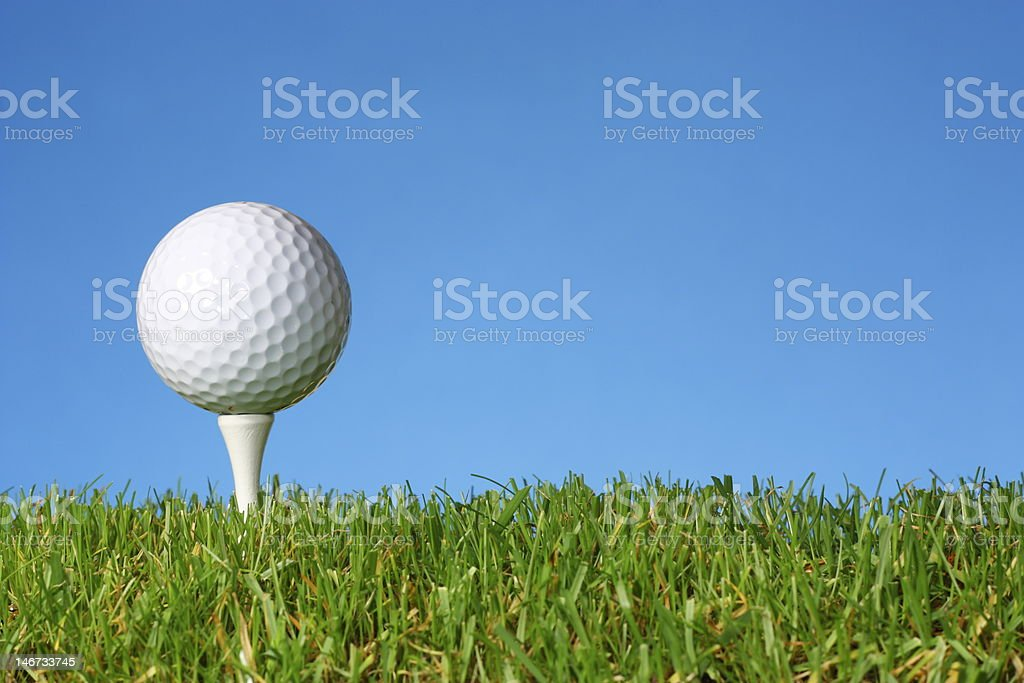 Golf ball on a white tee with lush grass. royalty-free stock photo