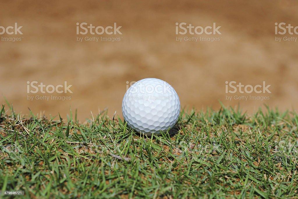 Golf ball on grass near sand  bunker stock photo