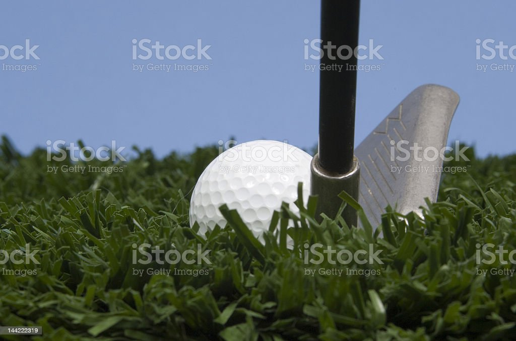 Golf ball on grass with club against blue sky royalty-free stock photo