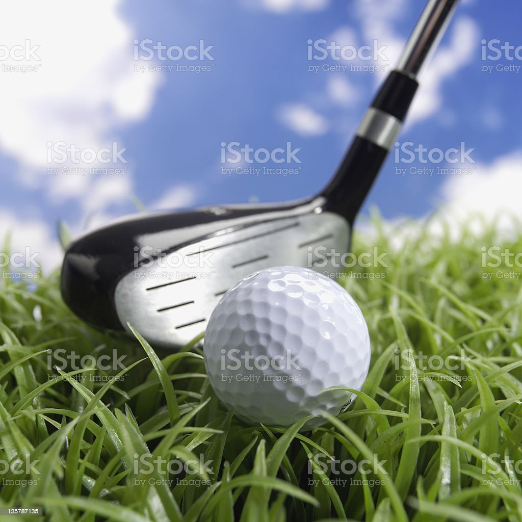Golf ball on grass with hybrid driver royalty-free stock photo