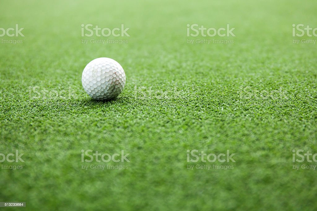 Golf ball on green field during sunset stock photo