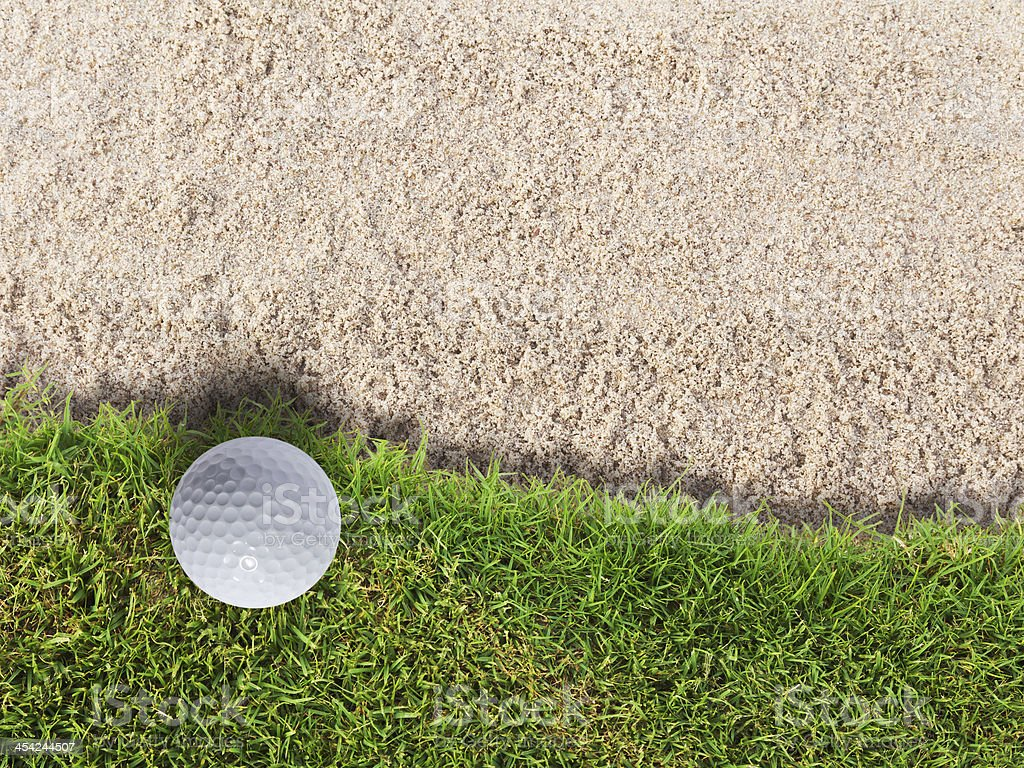 Golf ball on green grass near sand bunker stock photo