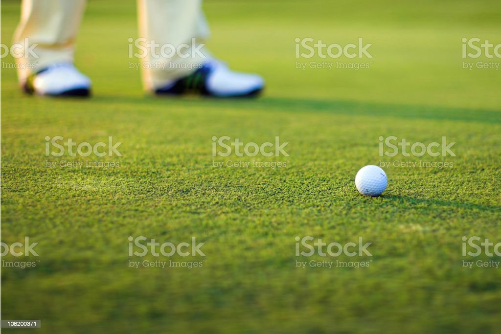 Golf Ball on Green Grass with Blurred Shoes in Background royalty-free stock photo