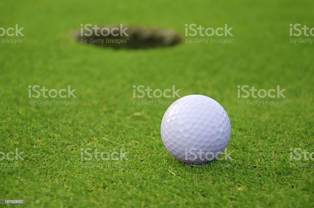 Golf ball on green with hole in background royalty-free stock photo