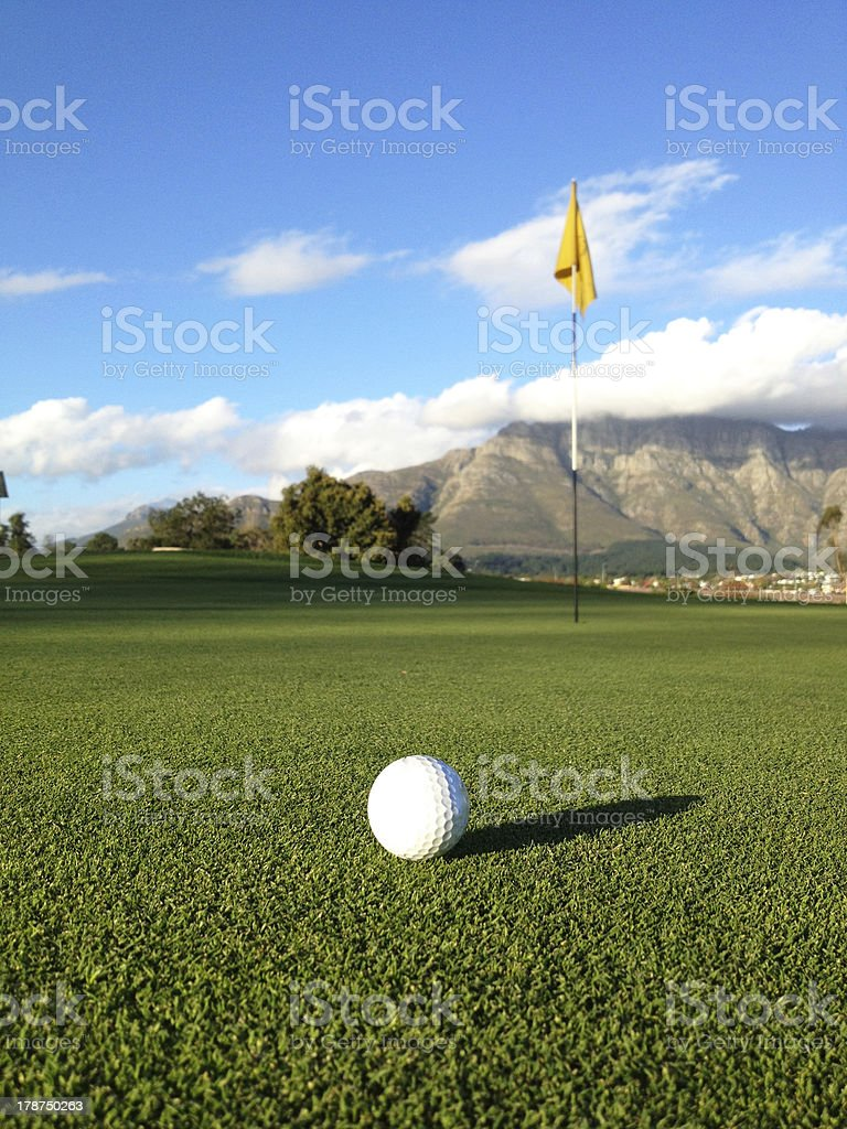 Golf ball on putting green near pin royalty-free stock photo
