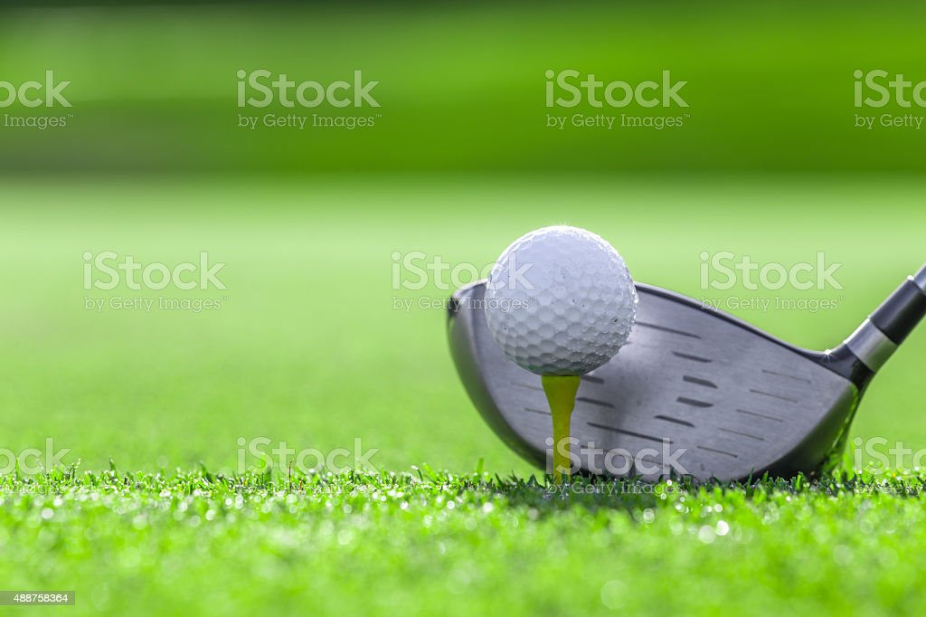 A close-up of a golf ball on a white golf tee against vibrant green...