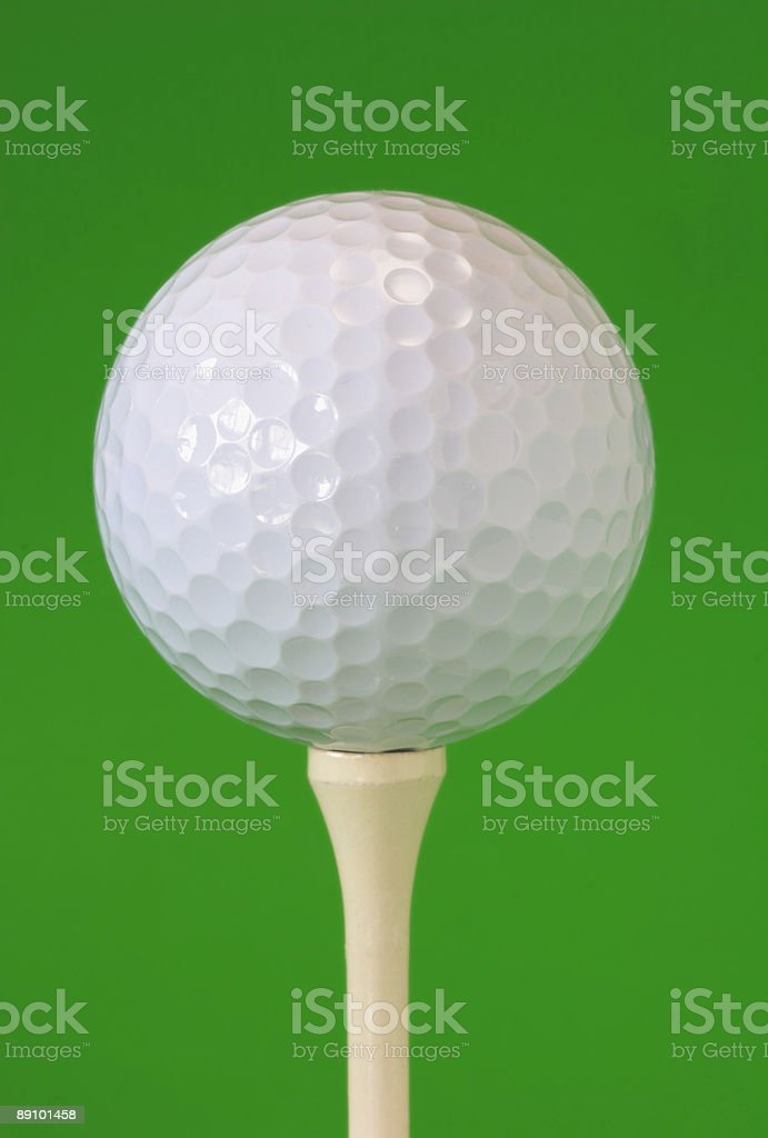 Golf Ball on Tee - Green Background royalty-free stock photo