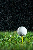 Golf ball on tee in rain