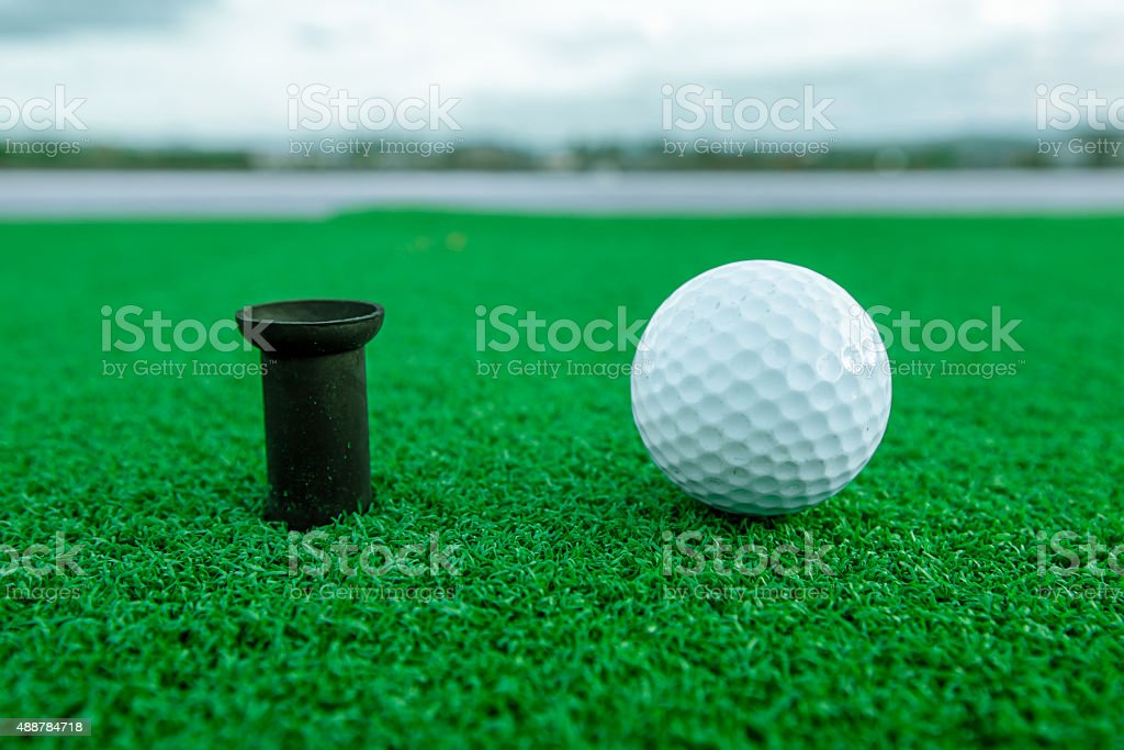Golf ball on tee on the artificial turf, Driving range stock photo