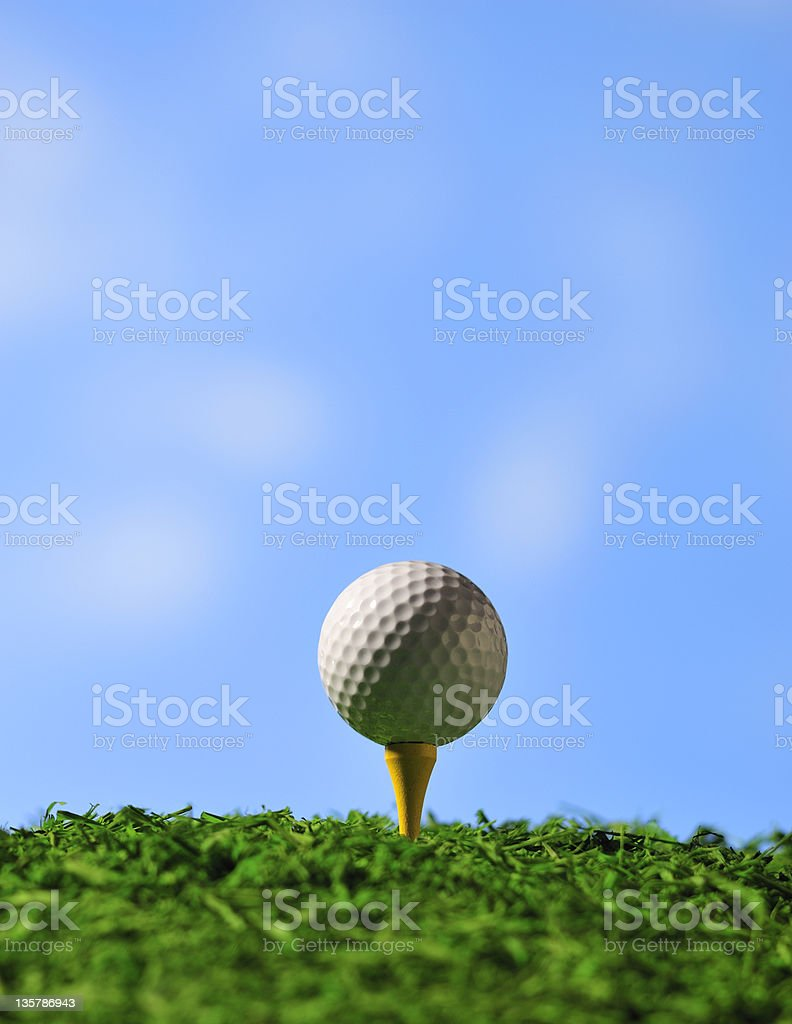 Golf ball on tee  with blue sky background stock photo