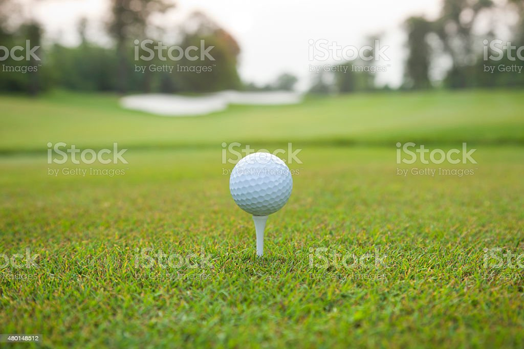 Golf ball on tee with defocused background stock photo