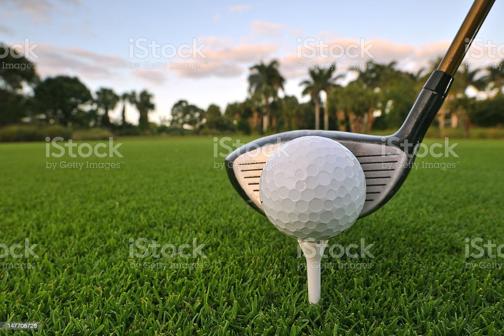 golf ball on tee with driver at dawn stock photo
