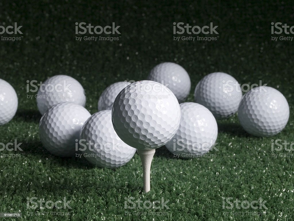 Golf Ball on Tee with Scattered Balls royalty-free stock photo