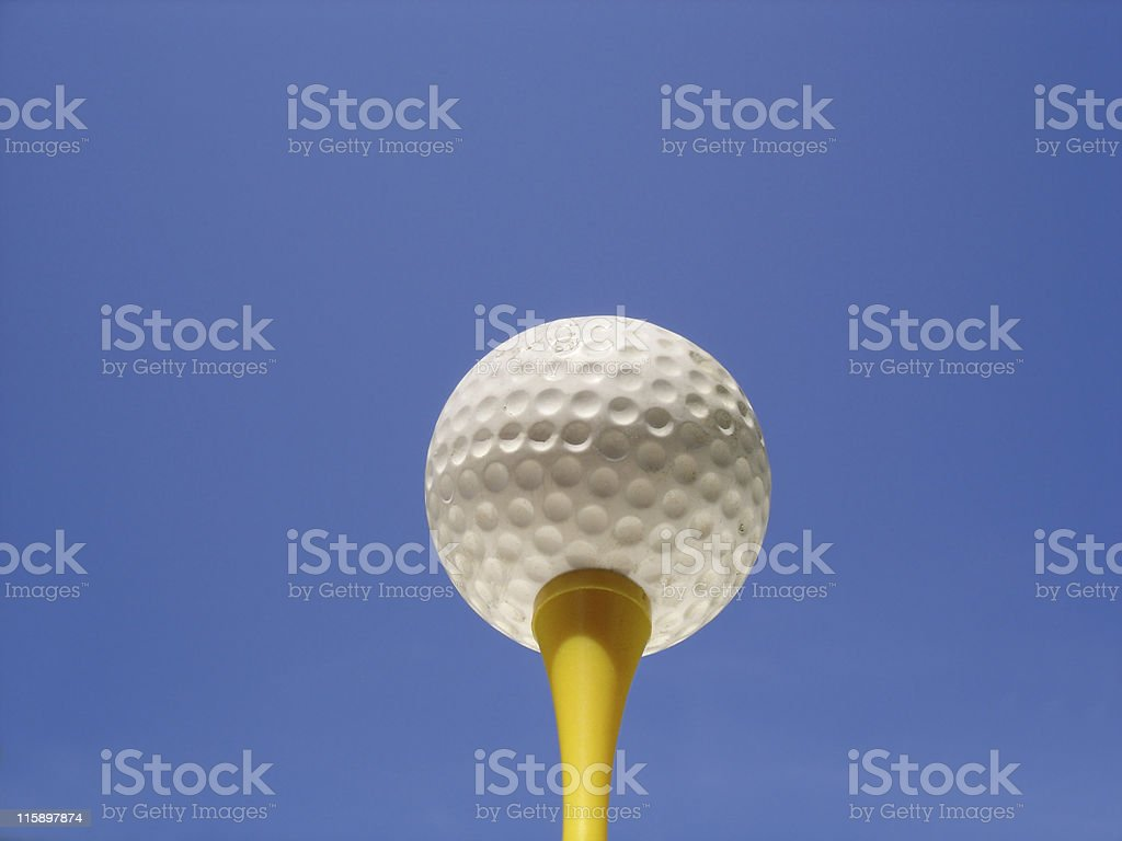 A golf ball on yellow tee against a blue sky. Negative space...