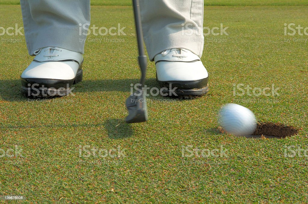 golf ball putting into hole royalty-free stock photo