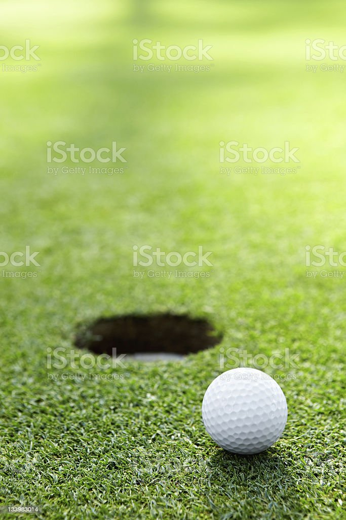 Golf ball sitting next to the hole stock photo