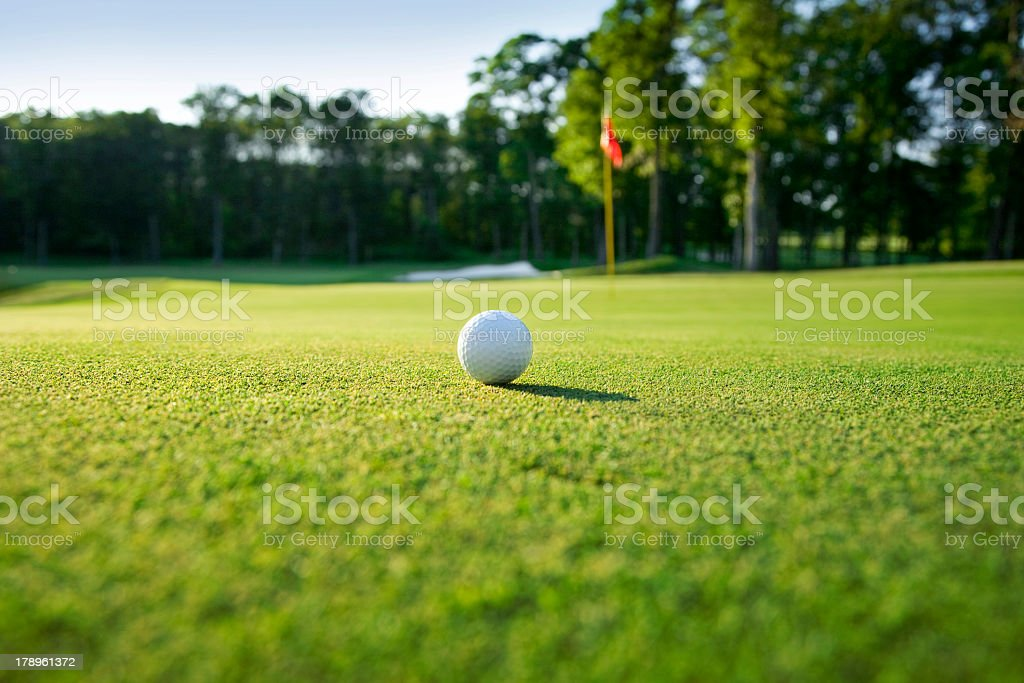 Golf ball sitting on a green with the flagstick nearby stock photo