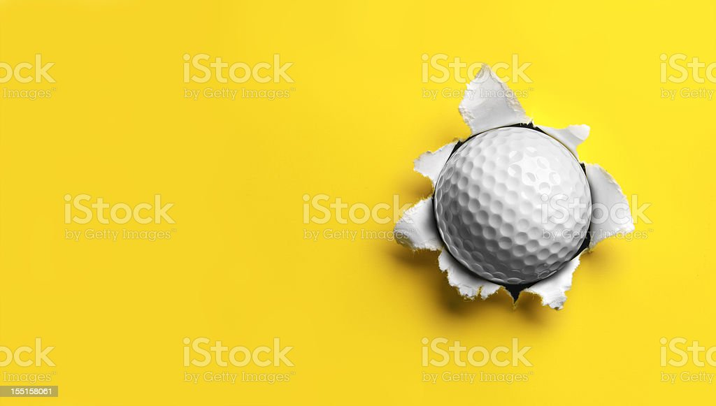 Golf Ball stuck in Yellow Paper stock photo