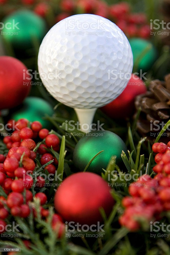 Golf ball surrounded by Christmas decorations royalty-free stock photo